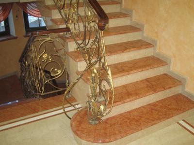 Фото изготовление и укладка мраморной лестницы с ограждением из художественной ковки и деревянными перилами.