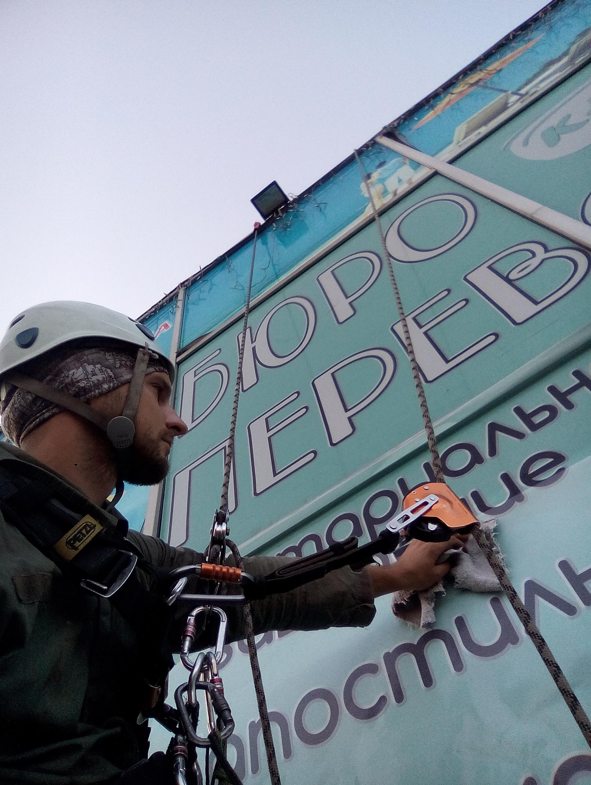 Фото Поклейка рекламы на стекло фасада.